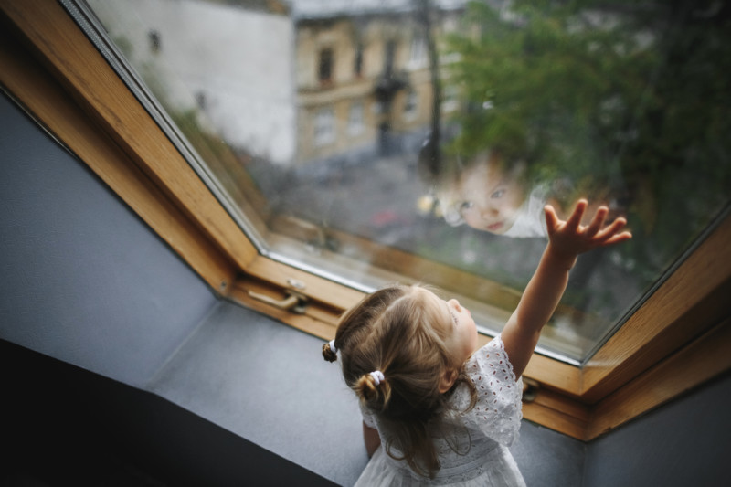 A little girl is looking out of the window